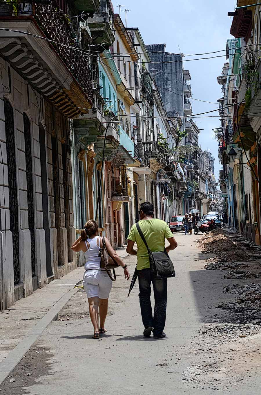 A couple walks in an Old Havana residential neighborhood